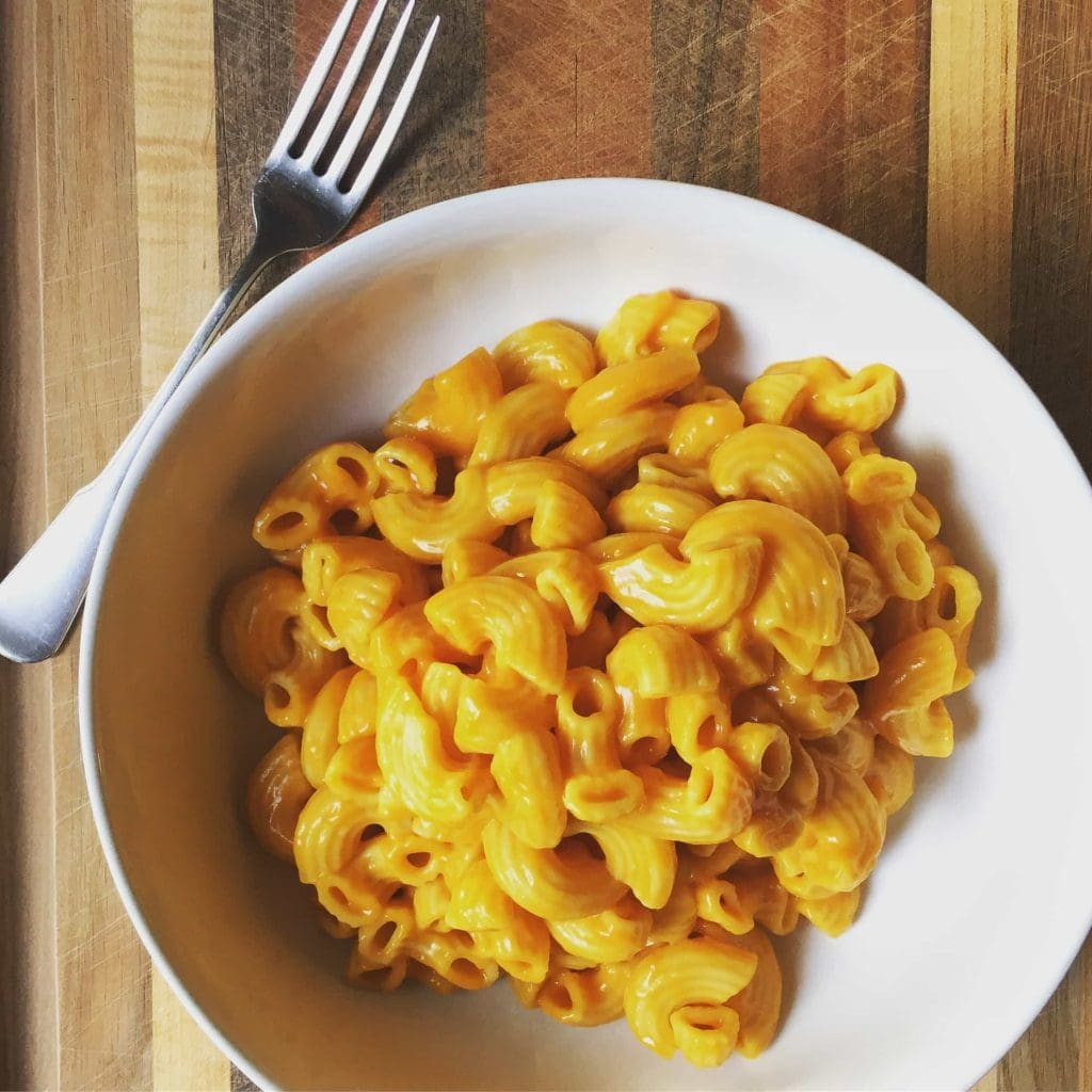 vegan mac and cheese in white bowl with metal fork on wooden background