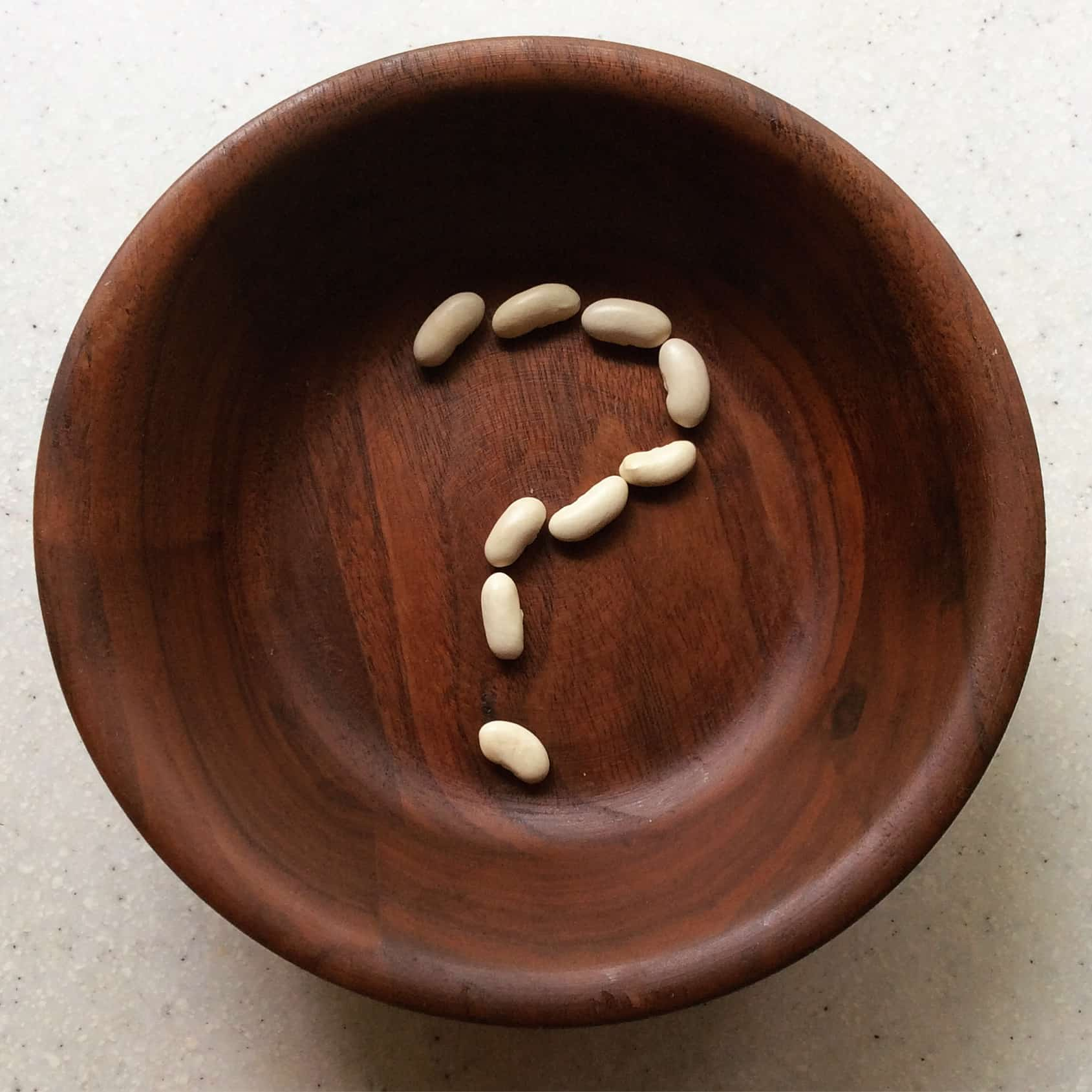 beans forming a question mark in a wooden bowl
