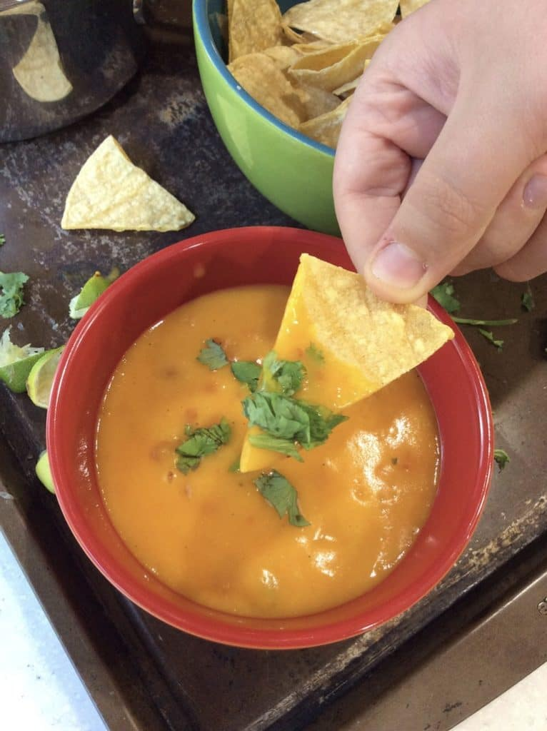 plant based queso in red bowl, chips, limes and cilantro - on tray