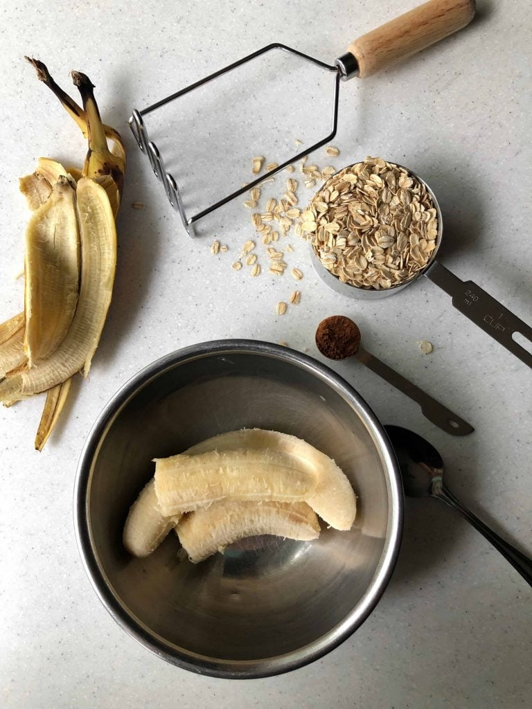 peeled bananas, cinnamon, rolled oats, spoon and masher