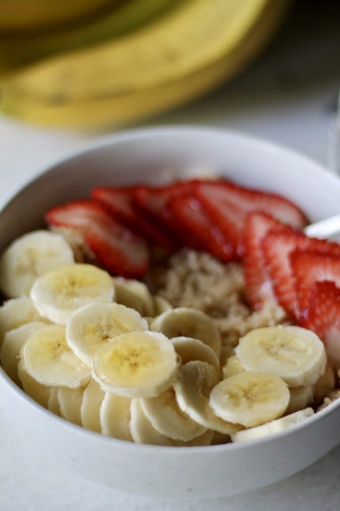 Breakfast Couscous Bowl with Banana and Strawberries with bananas in background