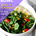 hash browns in a white bowl with sautéed spinach, corn, tomato