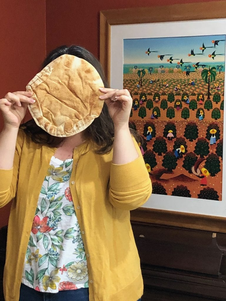 Abi holding a giant bread over her face