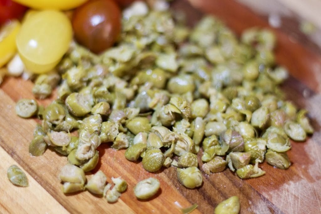 chopped capote capers on cutting board