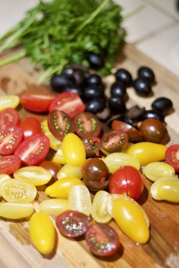 sliced tomatoes, olives and parsley on cutting board
