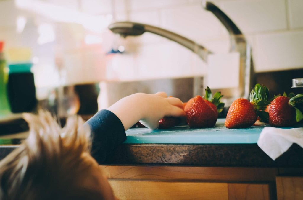 little child grabbing a freshly washed strawberry off the kitchen counter