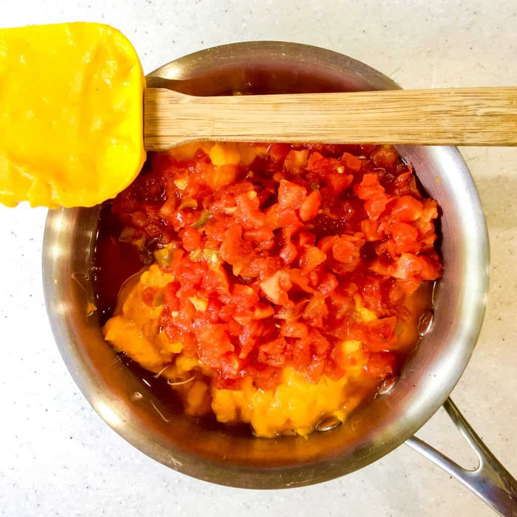 pot with tomatoes and spatula